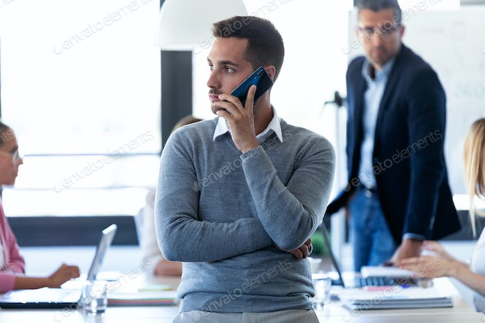 Handsome young businessman talking on mobile phone on coworking space.