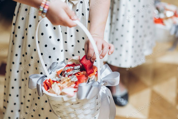 Girl in dress holding basket with petals of roses