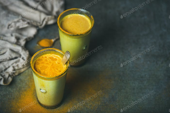Golden milk with turmeric powder in glasses over grunge background