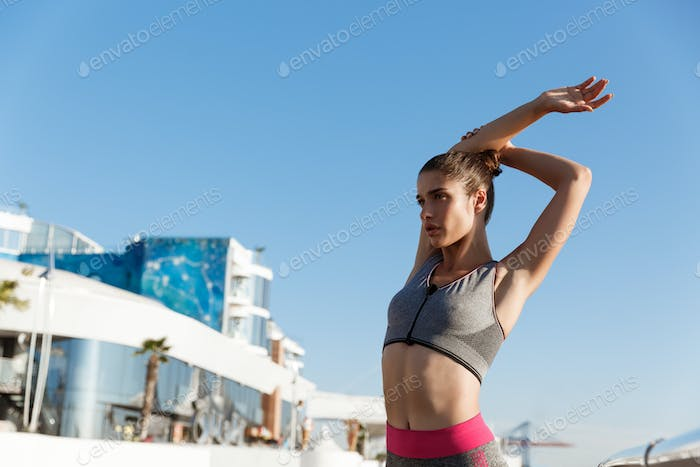 Low angle shot of attractive fit woman in sports bra and leggings, doing stretch exercises before