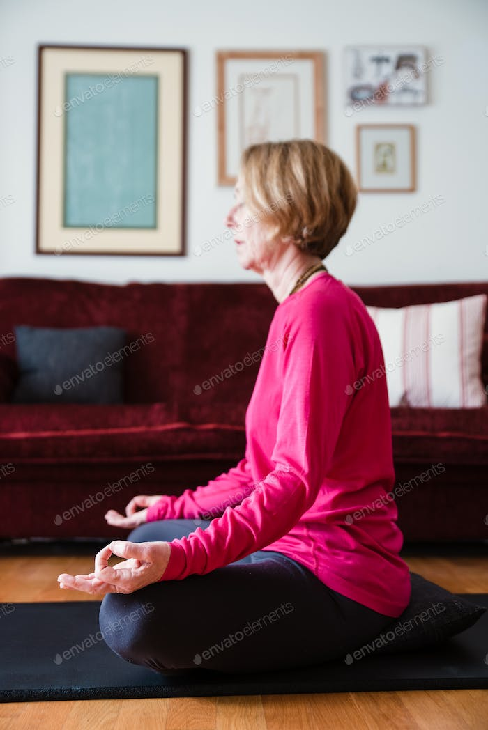 Middle aged woman sitting in lotus position on yoga mat in her living room.