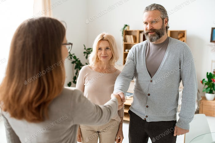 Mature casual couple greeting their real estate advisor in office