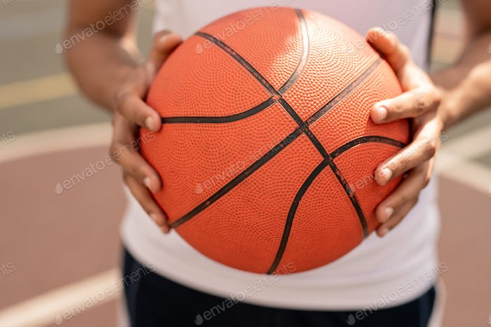 Ball for playing basketball in hands of young active player