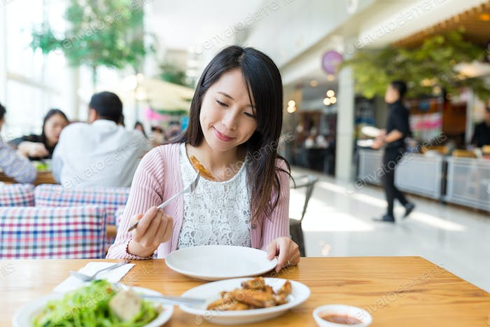 Woman enjoy her meal at restaurant