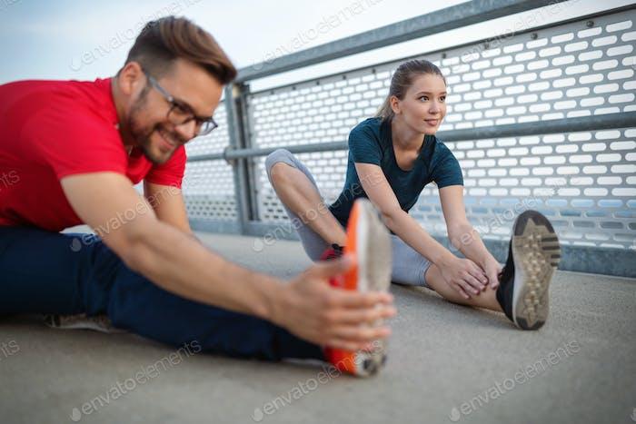 Fitness, Sport, Training und Lifestyle-Konzept. Fit Paar Freunde Stretching im Freien