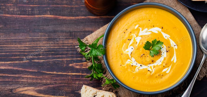 Pumpkin and carrot soup with cream and parsley on dark wooden background Top view Copy space