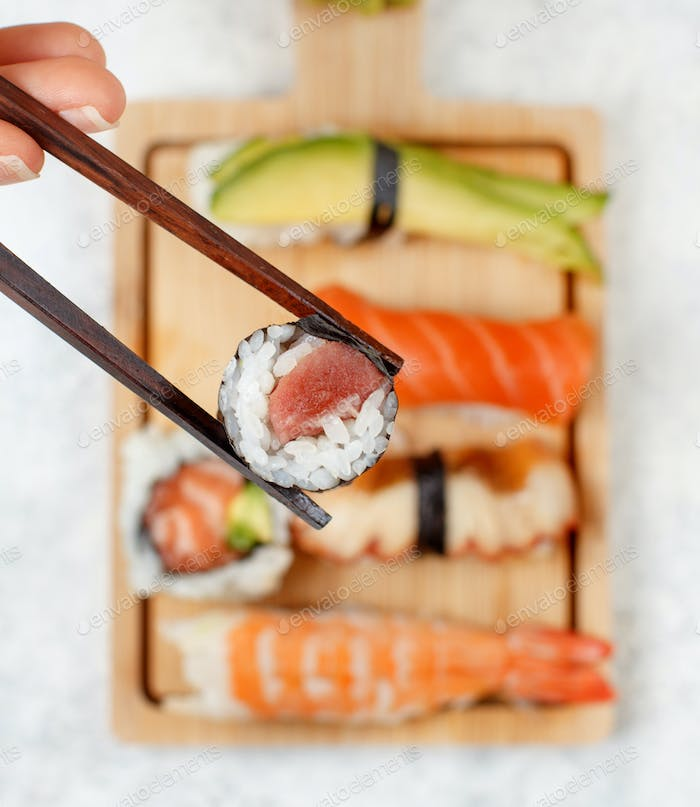 Hand taking roll with chopsticks from a plate