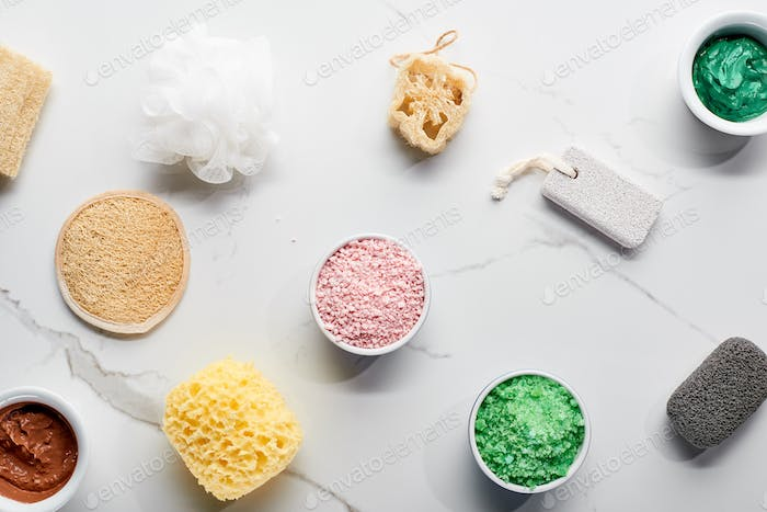 Top View of Color Bath Sponges, Pumice Stones, Bath Salts And Clay Mask on Marble Surface