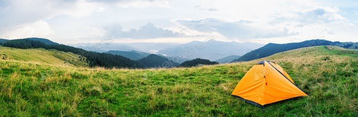 Orange tent on a meadow with green grass in mountains