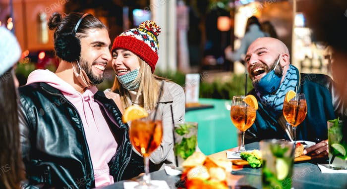 Young friends talking at winter cocktail bar outdoors wearing open face mask