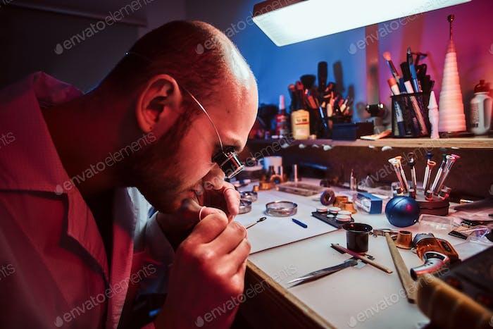 Fokussierter nachdenklicher Meister arbeitet an der Uhr des Kunden in seiner Werkstatt.