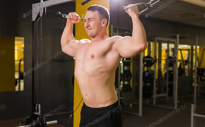 Young handsome man training in gym