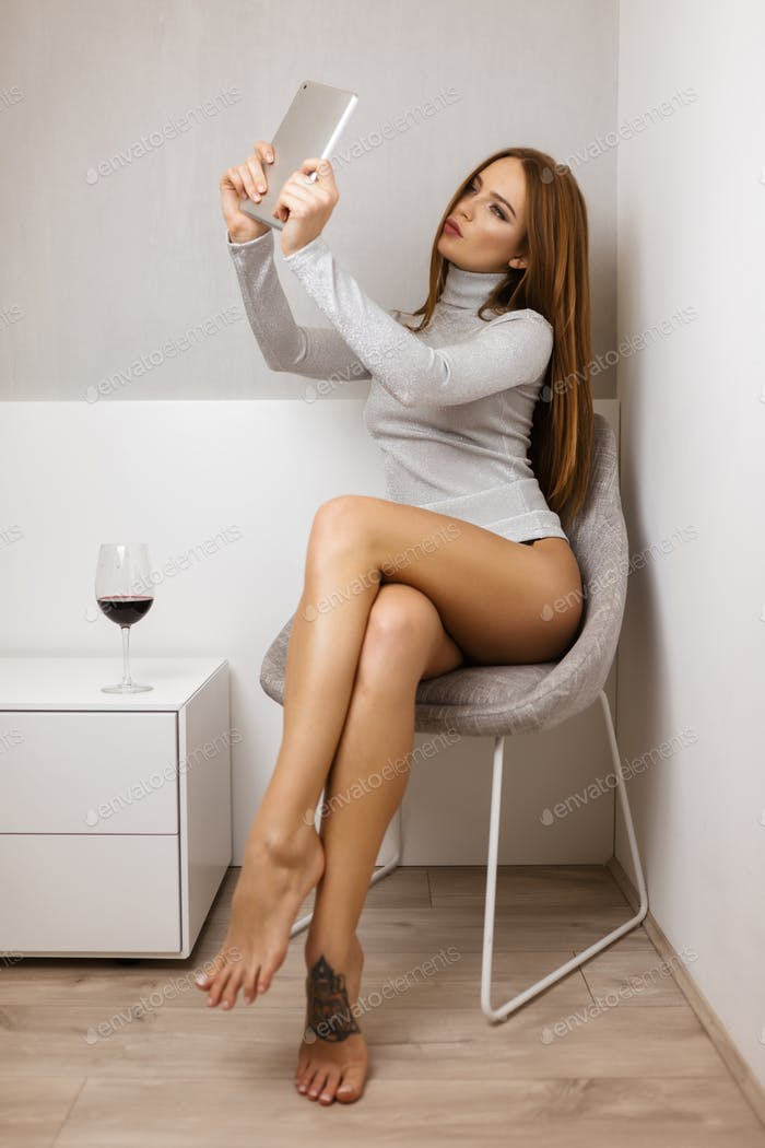 Beautiful lady in sweater sitting and taking photo on frontal camera with glass of red wine near