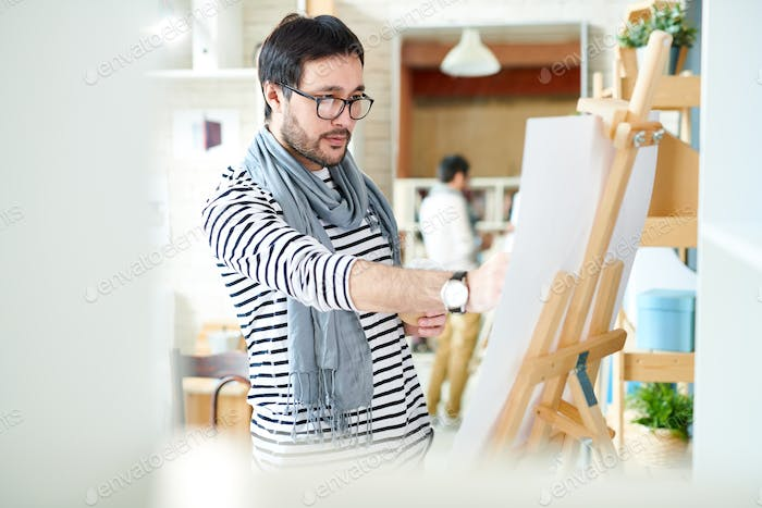 Trendy man painting on easel
