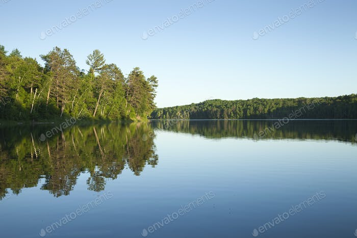 Calm Clear Northern Minnesota Lake with Pines and Birch