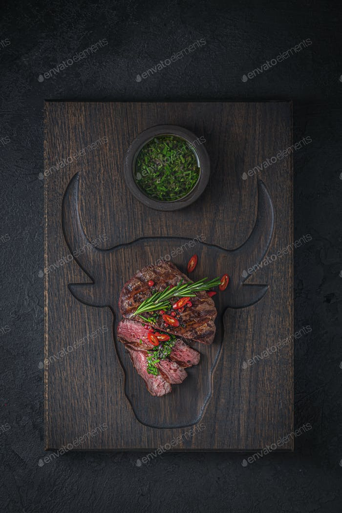 Fillet mignon with chimichurri sauce on wooden cutting board