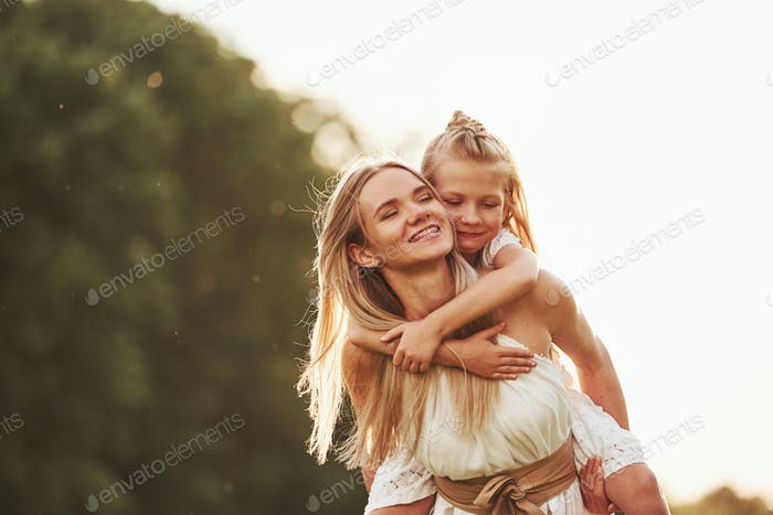 Mother and daughter enjoying weekend together by walking outdoors in the field. Beautiful nature