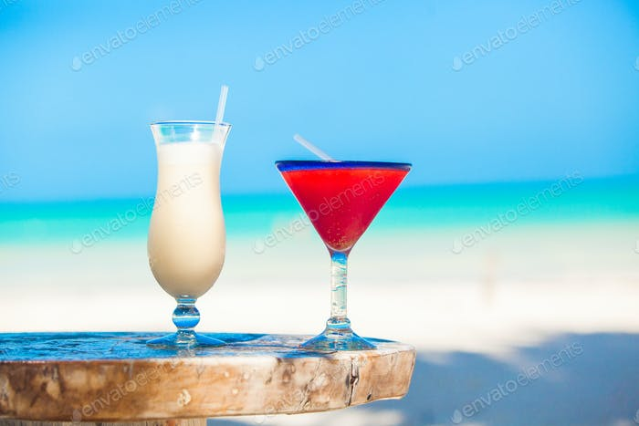Two cocktails: pina colada and strawberry margarita on wooden table