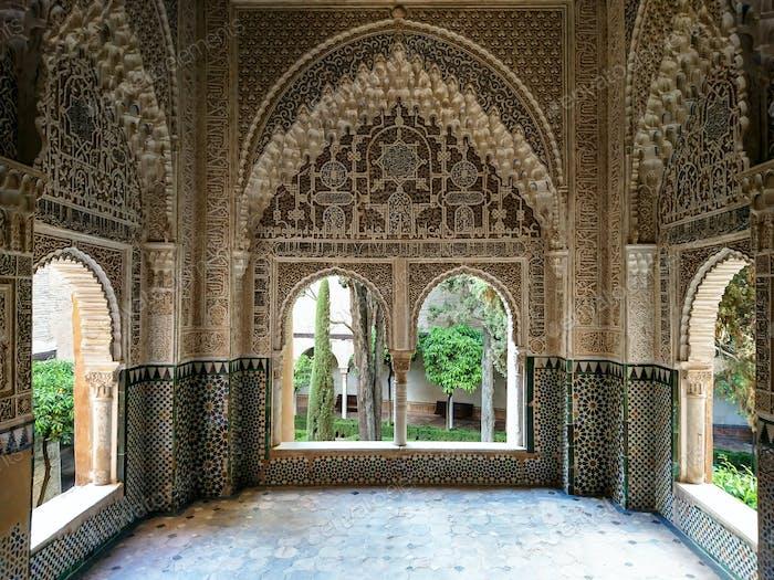 Detail einer Wand mit arabischen Symbolen und bunten Mosaiken