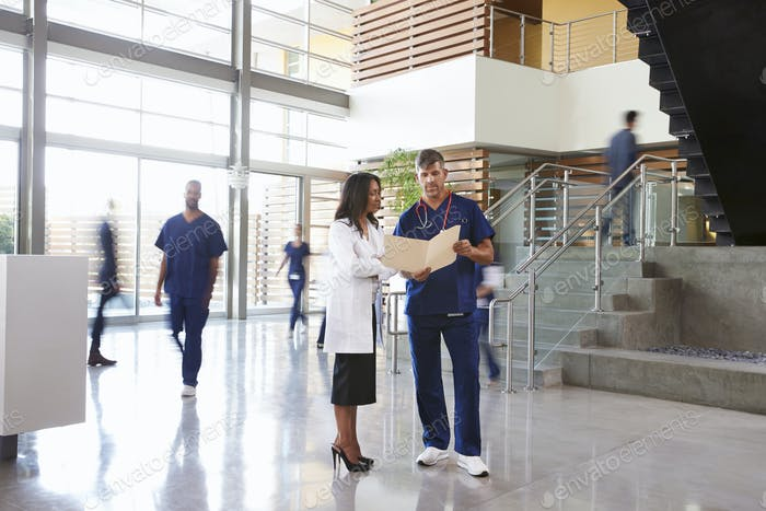 Two healthcare workers talk in the lobby of a busy hospital