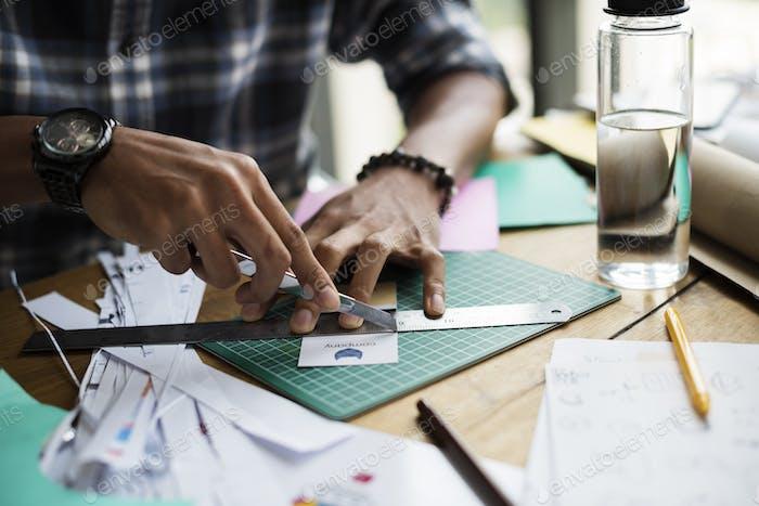Hands Holding Cutter Cutting Paper