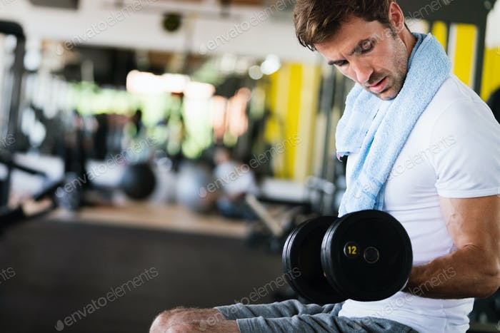 Muscular man working out in gym doing exercises with dumbbells at biceps