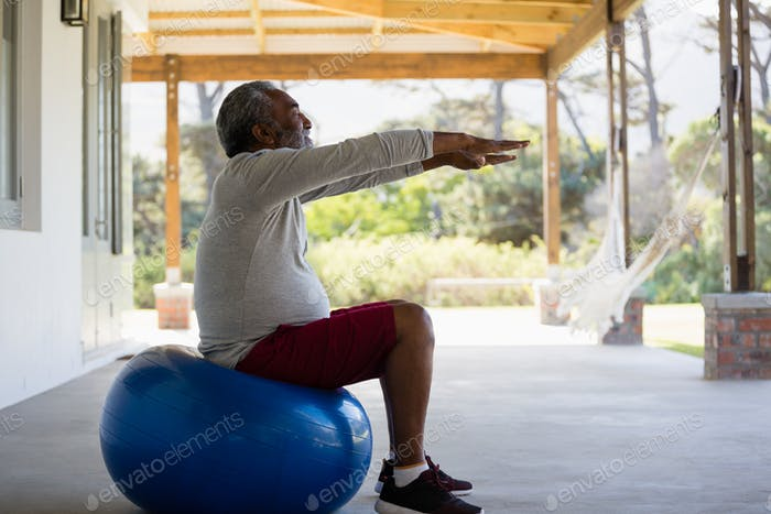 Senior man exercising on exercise ball in the porch