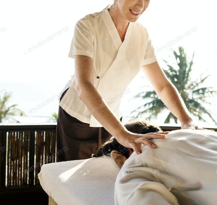 Weibliche Masseurin gibt eine Massage in einem Spa