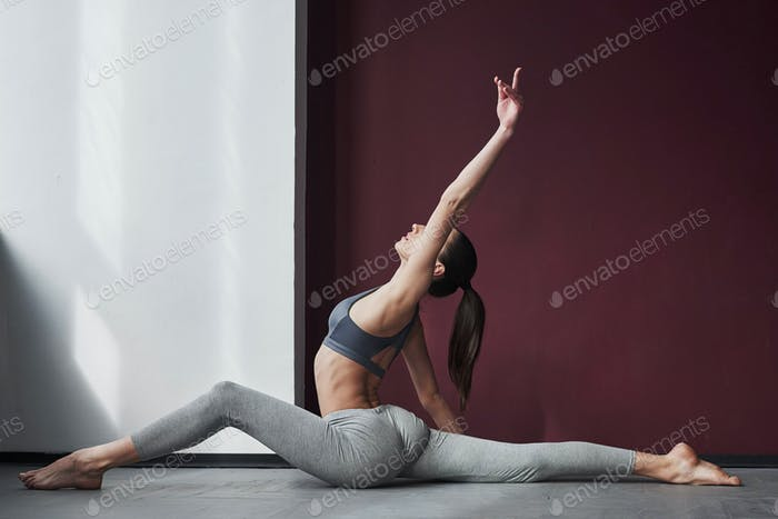 Side view. Girl with good fitness body type have exercises in the spacey room