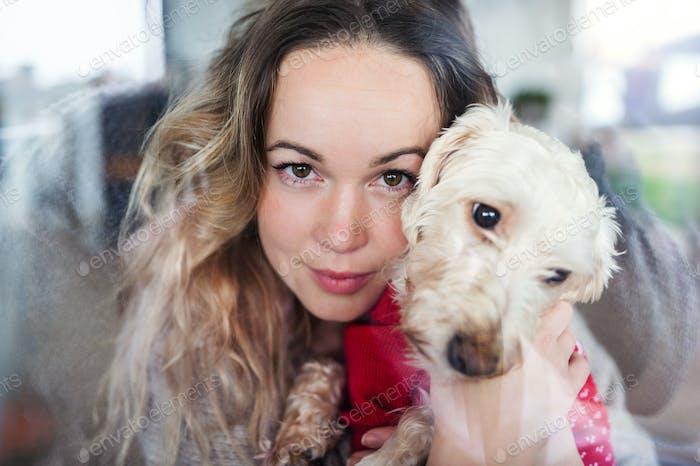 Junge Frau entspannt drinnen zu Hause mit Haustier Hund