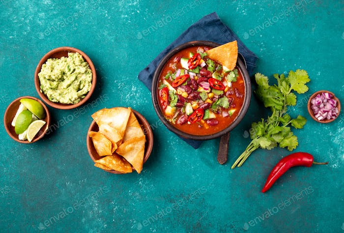 Mexican black bean soup with tomato, avocado and totopos. Blue background, top view