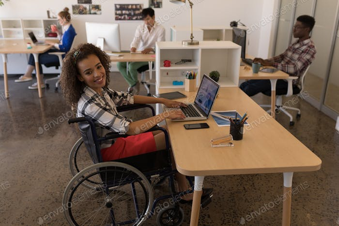 Side view of young disabled mixed-race female executive using laptop at desk in modern office