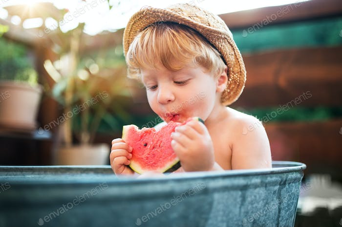 Small boy with a hat in bath outdoors in garden in summer, eating watermelon.