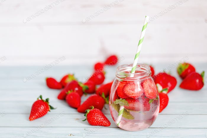 Glasses of strawberries, mint infused water with ice.
