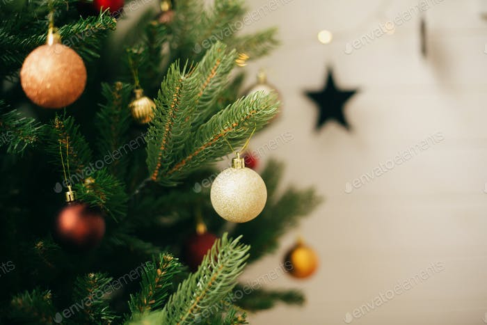 Modern golden baubles on Christmas tree