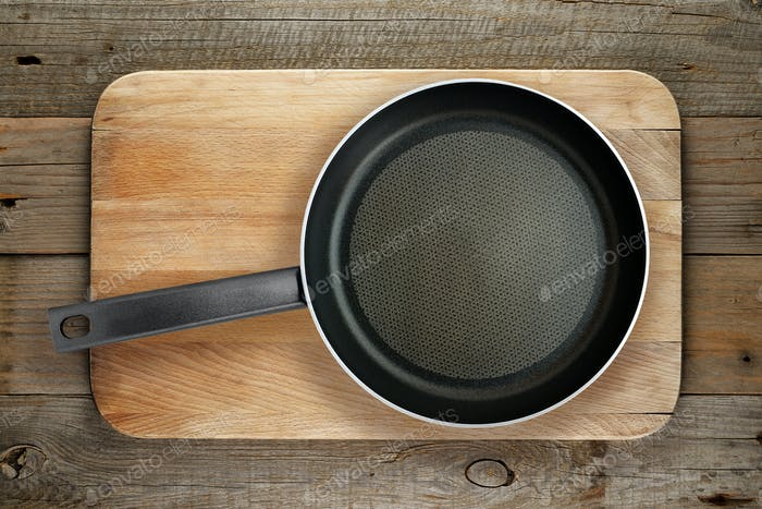Frying pan on wooden chopping board
