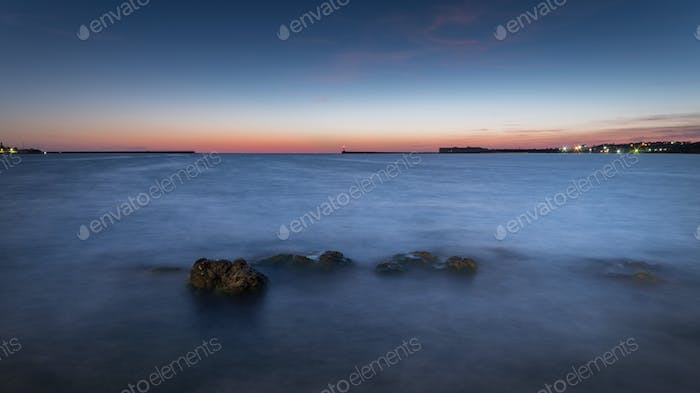 View of the bay with misty water in the evening after sunset