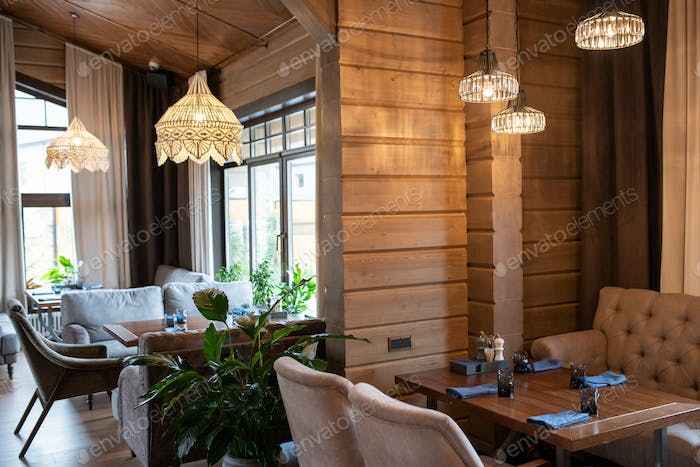 Corner of modern luxurious restaurant with wooden tables served for guests