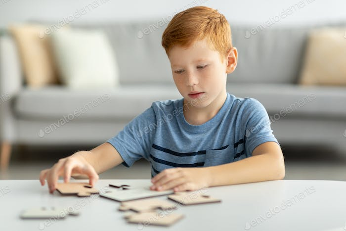 Preteen boy playing with wooden puzzles at home
