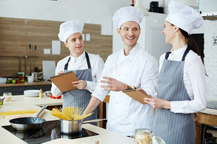 Cheerful cooking specialists discussing pasta recipe