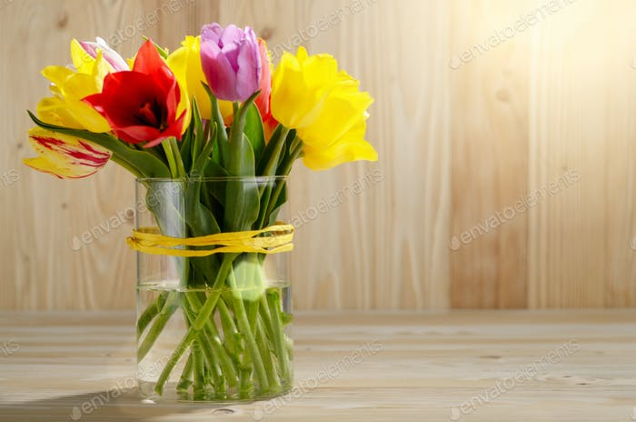Bunch of Colorful tulip flowers in glass vase on wooden table ba