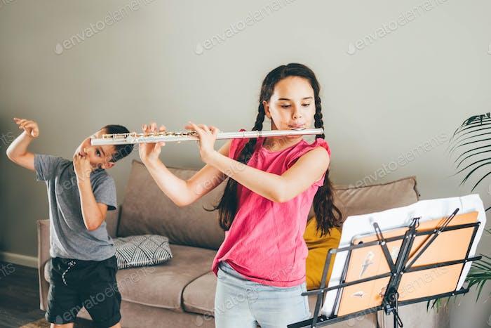Mädchen spielt Flöte. Bruder necken seine Schwester Land Spaß zu Hause.
