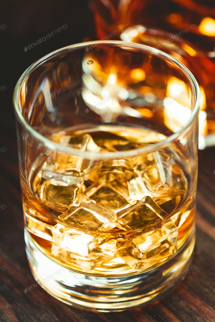 Whiskey with ice cubes in a glass ona wooden table.