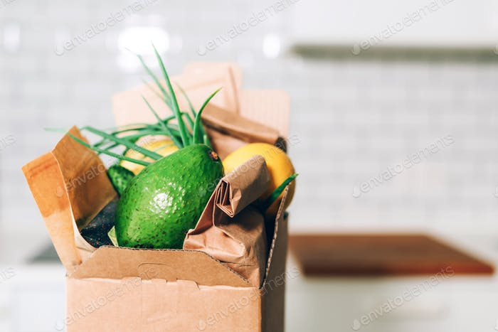 Spendenbox mit gesunder Nahrung auf weißem Küchenhintergrund. Raum kopieren. Lebensmittellieferservice während