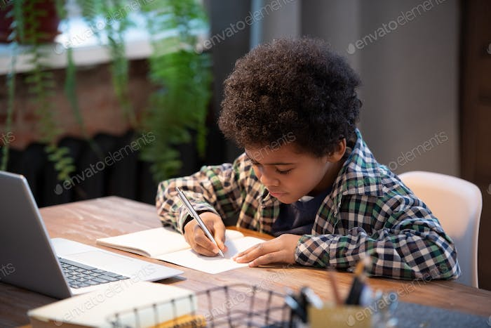 Contemporary African schoolboy in casualwear making notes in copybook