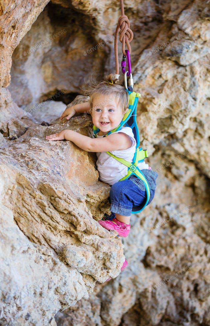 Happy little girl climbing on cliff