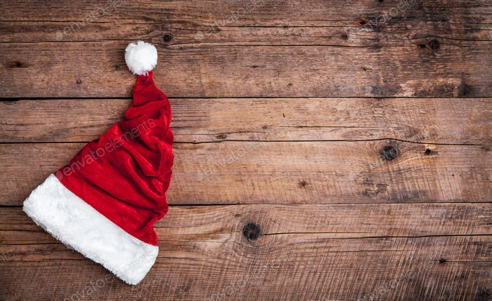Santa red hat on wooden background, holiday Christmas