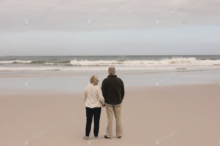 Senior couple standing  hand in hand at the beach with ocean in the background