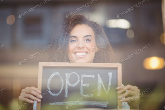 Portrait of a waitress showing chalkboard with open sign at the coffee shop