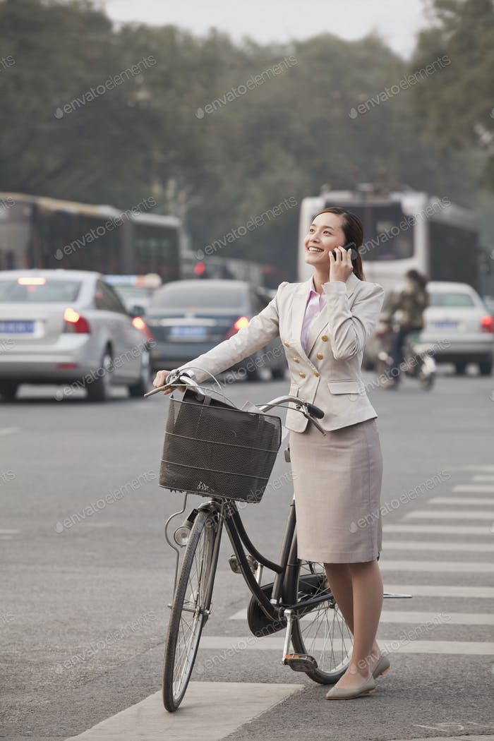 Young Business Woman standing with a Bicycle, Beijing, China